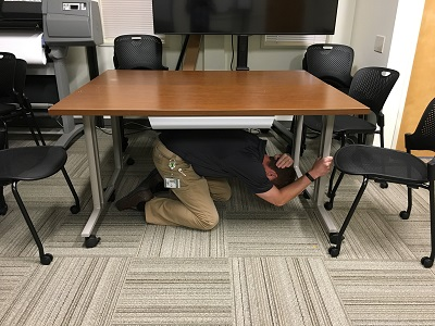 Ducking under a table during earthquake drill